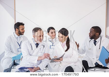 Team of cheerful physicians sitting on seats and speaking with each other during meeting in white room of clinic