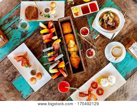 Top view of delicious organic food served for breakfast on rustic wooden table. Coffee, eggs, fruits, juice, croissants and jam flat lay.