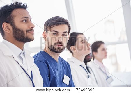 Serene bearded surgeon sitting with pensive therapeutics during meeting in office of hospital