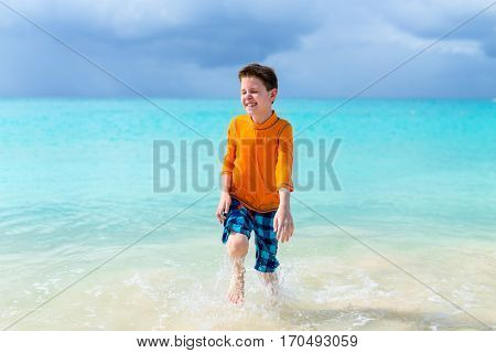 Cute boy in sun protection rash guard at tropical beach on summer vacation