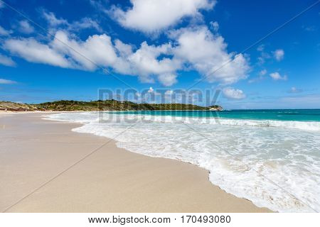 Idyllic tropical beach with white sand, turquoise ocean water and blue sky at Antigua island in Caribbean
