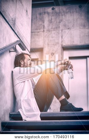 Worried doctor sitting on stairs in hospital