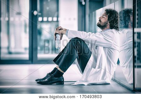 Side view of worried doctor sitting on floor in hospital