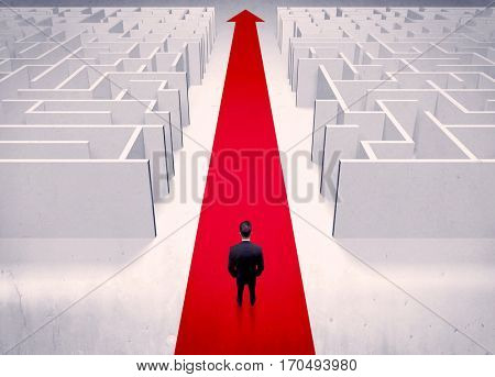 An adult elegant businessman standing on a red carpet arrow pointing ahead through a street with maze on two sides concept