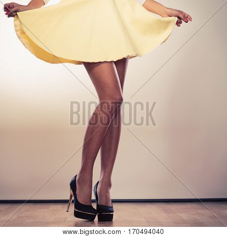 Attractive slim legs of mixed race african caucasian woman girl in skirt on high heels.
