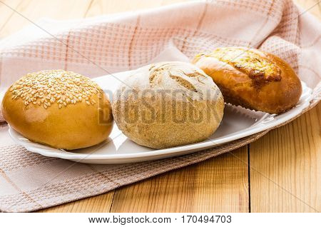 Three Different Buns In Glass Dish And Pink Towel