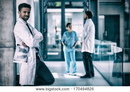 Portrait of doctor holding x-ray while standing against wall in hospital