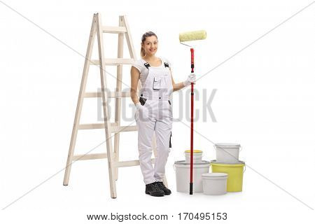 Full length portrait of a female decorator with a paint roller standing in front of a ladder isolated on white background