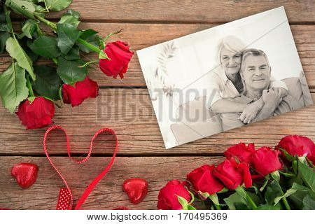 red roses against smiling woman embracing husband sitting on couch