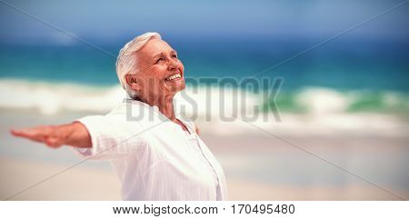 Side view of mature woman posing with outstretched arms at beach