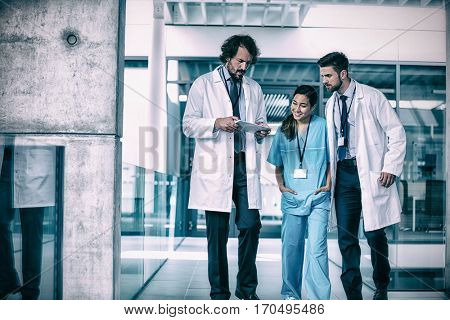 Doctor holding digital tablet having discussion with colleagues in hospital