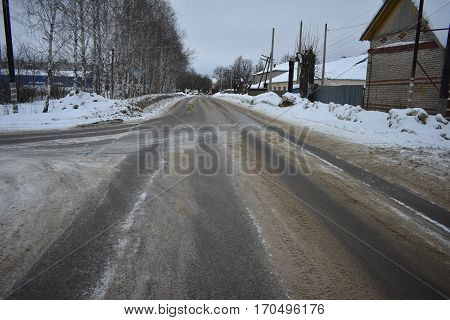 the road is tarmac sleet a lot of snow black and the gray asphalt of