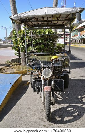A motorcycled is tcoverted into a three wheeled vehicle and used as a taxi to transport riders around the city of Mazatlan, Mexico.