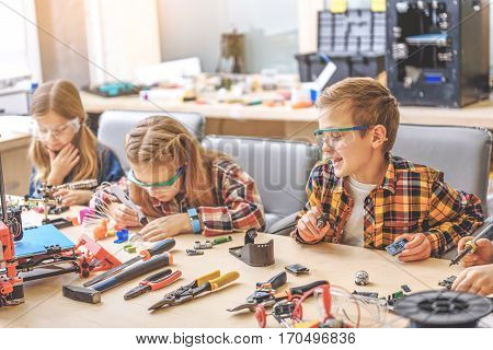 Smiling boy is sitting beside concentrated girls and looking at them. He holding soldering iron