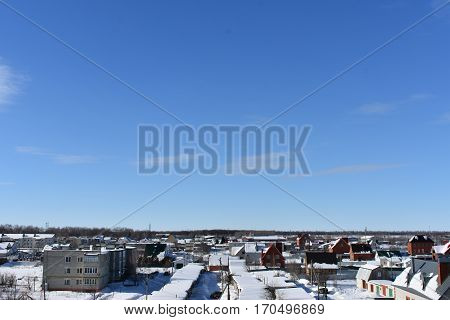 winter snowy frozen city on the background of blue sky with clouds;building, structure, facility, and the infinite horizon abstract background ;winter ;frozen ice ;clear,