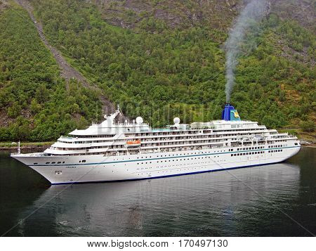 Geiranger, Norway - June 3, 2009: The cruise ship Amadea anchored in Geiranger Fjord in Norway. The tender boats are lowered into the water to take passengers for a shore excursion ashore. Many exhaust gas flows from the chimney of the ship.
