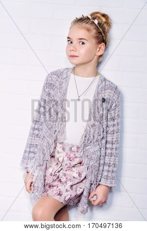 Pretty eight year old girl stands by a white brick wall and smiling. Kid's fashion.