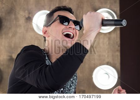 Male Singer In Sunglasses Sings On Scene In Projectors Lights