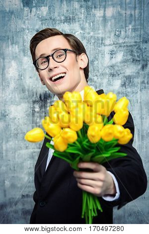 Excited handsome man in an elegant suit giving a bouquet of yellow tulips. Valentine's Day, Women's Day, Mother's Day. Wedding concept.