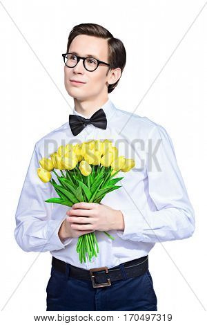 Handsome young man in an elegant suit with a bouquet of yellow tulips. Valentine's Day, Women's Day, Mother's Day. Wedding concept. Isolated over white.