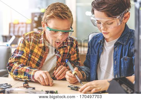 Wondered boy is sitting beside his interested neighbor at table full of tools. Young technician holding soldering iron