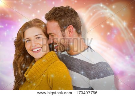 Close up of happy young couple embracing against glowing background