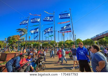 San Francisco, California, United States - August 14, 2016: People crowd at Pier 39 with waving flags and sign destination of San Francisco Pier 39. Fisherman's Wharf is a popular tourist attraction.