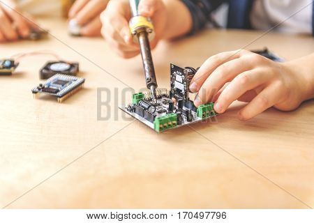 Child is near table. He holding soldering iron and renovating mainboard. Close up of his hands