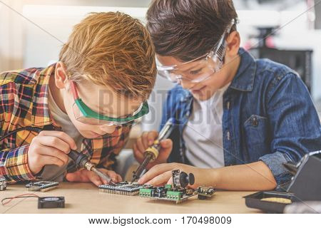 Smiling boys are sitting at table. They fascinatedly working together at small mainboard with soldering irons