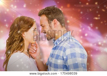 Happy young couple looking at each other and smiling against glowing background