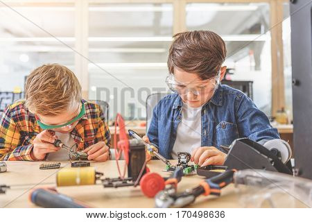 Serious concentrated children are sitting in workshop. They working with soldering irons and repairing small mainboards
