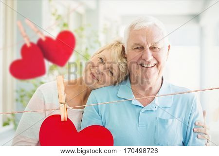 Composite image of happy senior couple together with red hearts hanging on line
