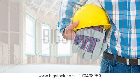Mid section of construction worker holding hard hat and gloves