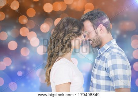Happy young couple rubbing nose against glowing background