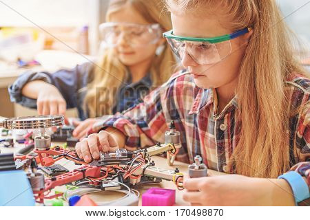 Serious interested girls are sitting near table with flying toy