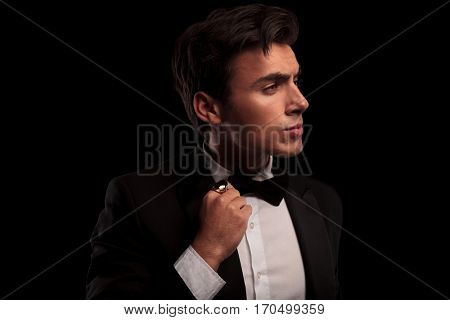 profile portrait of an elegant man fixing his bow tie and looks to side on black background