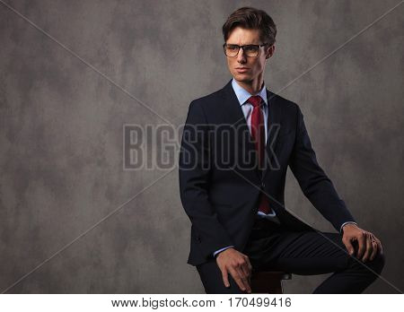 modern young business man wearing glasses and sits on a stool in studio, looking to a side away from the camera