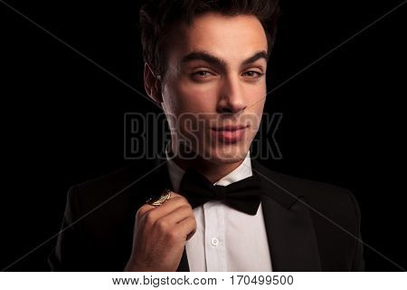 closeup picture of a young man in tuxedo fixing his bowtie and wearing a big golden ring on black studio background