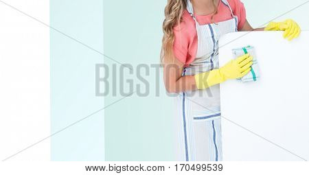 Mid section of woman in apron cleaning fridge against white and green background