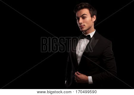 sexy man in tuxedo fixing his collar and looks at the camera on black studio background