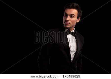 cool young man in tuxedo and bowtie posing in studio on black background