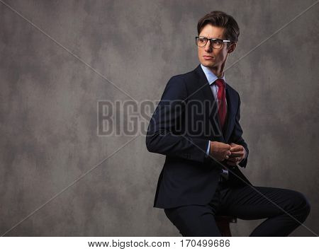 seated business man buttoning his suit and looks over his shoulder in studio, sitting on a stool