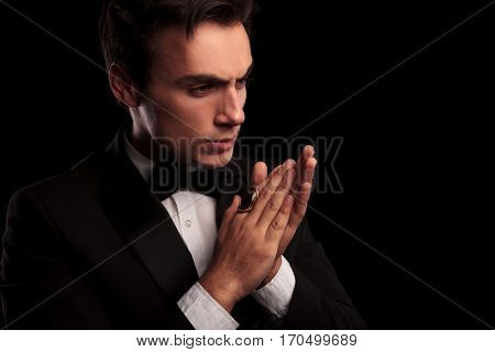 serious or angry elegant man in tuxedo and wearing big gold ring looking away from the camera while rubbing his palms