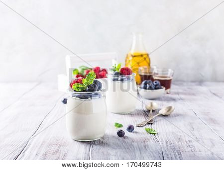 Natural yoghurt with berries on light gray background. Copy space. Healthy breakfast concept.