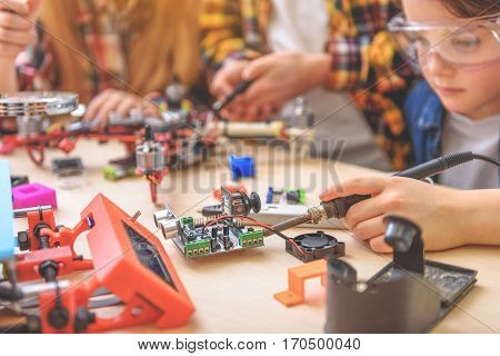 Serious boy is sitting among his friends. He holding soldering iron and repairing mainboard