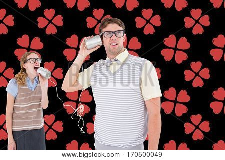 Couple talking on tin can phone against digital composite heart background
