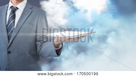 Mid section of businessman holding digital tablet against digitally generated sky background