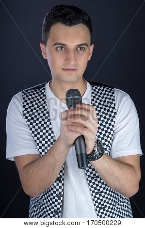 Young Male Black-haired Rock Singer Performs Singing To Microphone