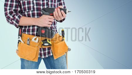 Mid section of handy man with tool belt holding a drill against blue background