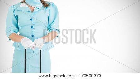 Mid-section of air hostess holding a suitcase against white background